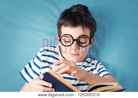 seven years old child lying with book on blue background