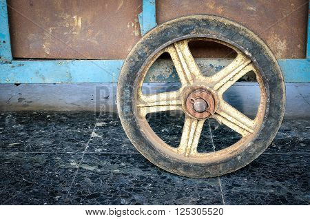 Old yellow wheel propped up on old grunge wall, Concept image
