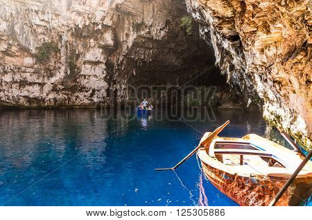 MELISSANI LAKE, KEFALONIA ISLAND, GREECE - August 9 2015: Boat with tourists on the blue lake inside the cave.