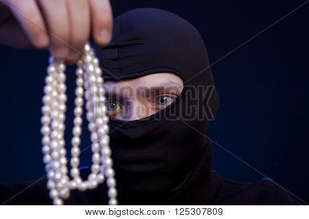 Thief. Man in black mask with a pearl necklace over dark blue background