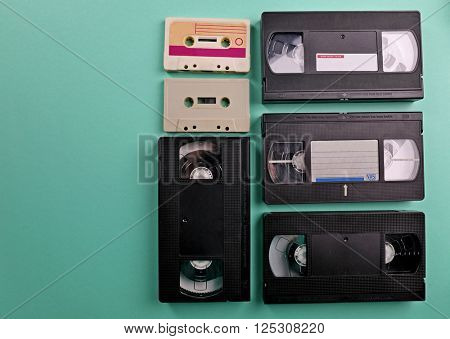 Set of old audio and video cassettes on turquoise background
