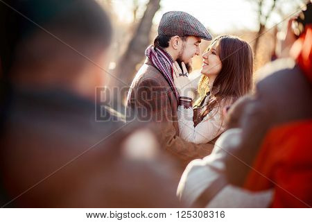 Stylish old fashioned couple among the crowd looking at each other outdoors in backlight at sunset. Man wearing tweed flat cap, brown clothes.