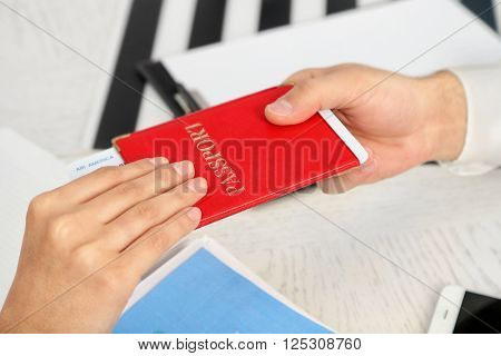 Agent giving passport and ticket to customer in the office of travel company