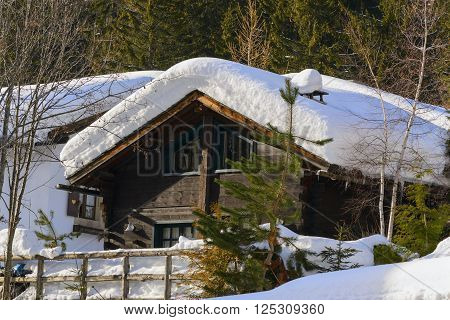 Winter ski chalet and cabin in snow mountain landscape