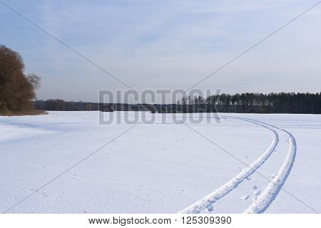 The track crossing a snow-covered field with the wood in the distance