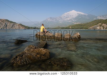 Bay to sea shore. Summer landscape. Tourist sits on a rock and looking at the mountains. Turkey Phaselis Bay, Mount Tahtali