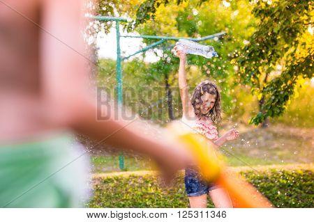 Unrecognizable boy splashing girl with water gun, fun in garden, sunny summer day, back yard