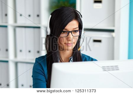 Portrait Of Young Female Operator With Headset Using Desktop Computer In Office