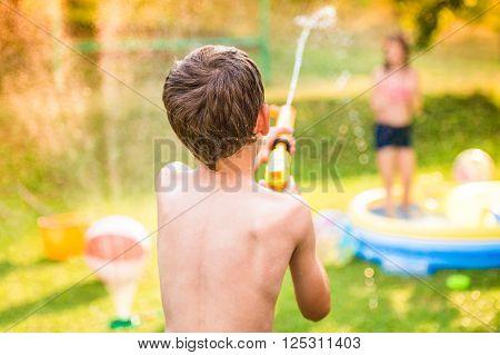 Boy splashing girl with water gun in garden swimming pool, sunny summer day, back yard, rear view