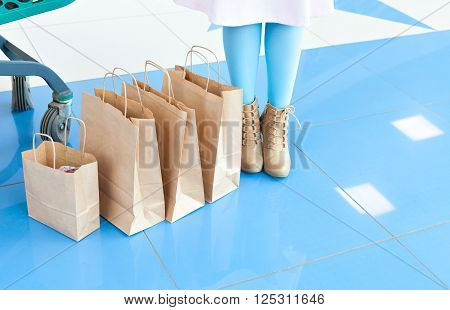Legs of a woman in a light blue tights and beige shoes near shopping bags. Shopping at the mall. mischievous mood. Copy space. Legs and bags