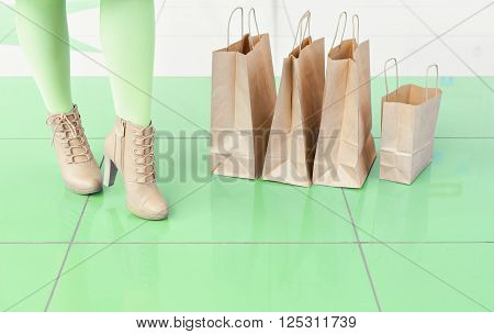 Legs of a woman in green tights and beige shoes near shopping bags. Shopping at the mall. mischievous mood. Copy space. Legs and bags