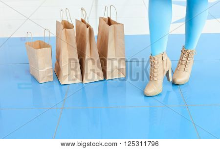 Shopping at the mall.  Legs of a woman in a light blue tights and beige shoes near shopping bags. mischievous mood. Copy space. Legs and bags
