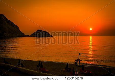 Sunset over beautiful beach of Petani in Kefalonia island, Greece.