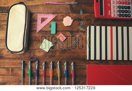 School set with notebooks, calculator and pencil case on wooden background