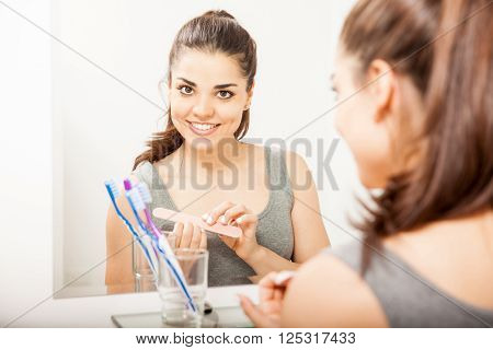 Cute Woman Filing Her Nails In The Bathroom