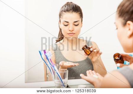 Woman Taking Pills In A Bathroom