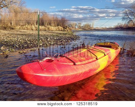 kayak and barbed wire  fence across river - St Vrain Creek below Longmont in Colorado