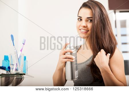 Woman Using Some Spray To Style Her Hair