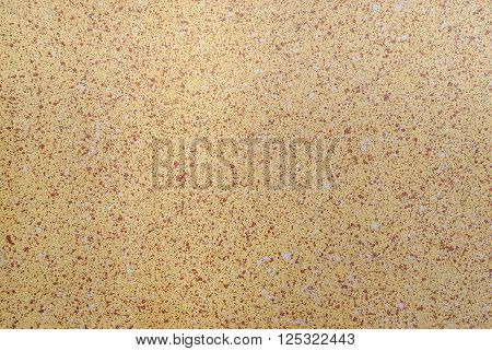 Abstract colored background of the spots of brown and white paint on the yellow plastered wall.