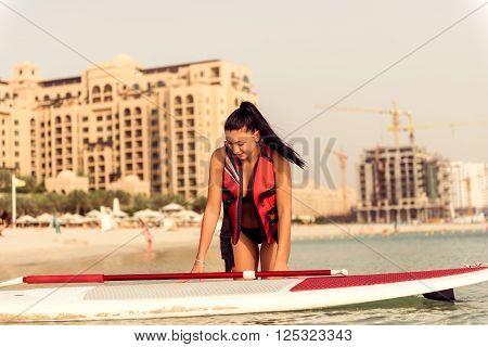 Attractive smiling woman paddling board in Dubai.