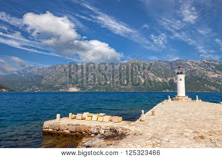 Stone wharf with a beacon against the sea and mountains Bay of Kotor Montenegro.