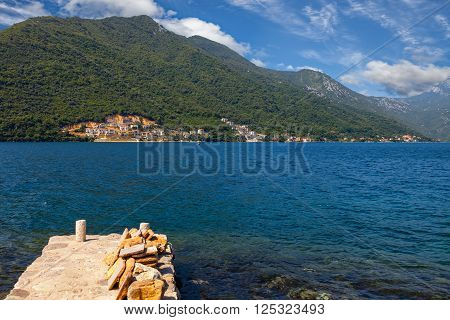 Stone wharf against the sea and mountains Bay of Kotor Montenegro.