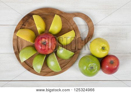 Composition of whole and sliced apples different color with wooden cutting board in top view