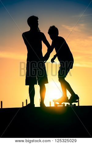 Young skater friends silhouettes at skate park. Teen boy standing while kid goes down on ramp with his skateboard.