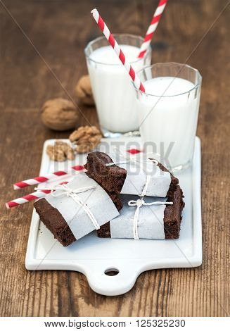 Chocolate brownie slices wrapped in paper and tired with rope, glasses of milk, stripe straws, walnuts on white ceramic board over rustic wooden background, selective focus