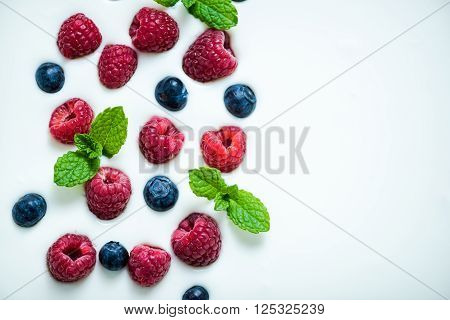 Fresh Raspberries And Blueberies With Mint On Yoghurt Background