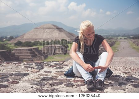 Young woman traveler resting on the top  after a long hard climb on one of  famous  ruins of ancient city Maya in Teotihuacan, Mexico with copy space. Mysterious smile on woman  face . Pyramid of Sun on background