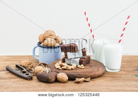 Chocolate brownie slices wrapped in paper and tired with rope, glasses with milk, stripe straws, enamel mug of walnuts on rustic wooden table, white background selective focus