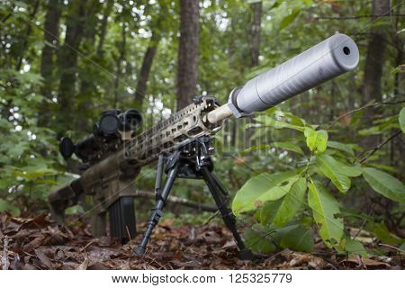 Semi automatic rifle with camouflage and a suppressor on the end