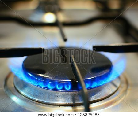 Closeup of burner with fire on kitchen gas stove.
