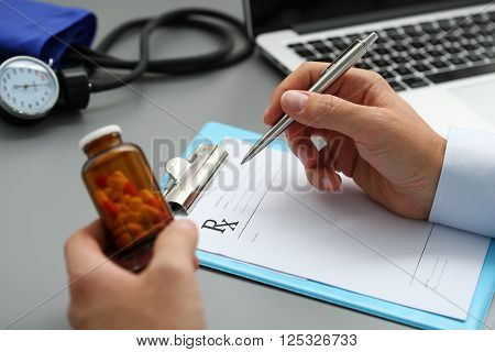 Male Medicine Doctor Hand Hold Jar Of Pills And Write Prescription