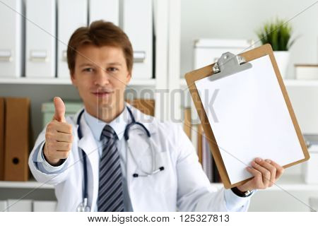 Male medicine doctor holding document pad in hand showing OK or approval sign with thumb up. High level and quality medical service best treatment and patient care concept. Satisfied happy intern