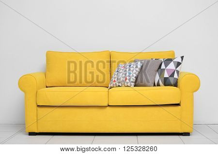 Yellow sofa with multicoloured pillows on white wall background