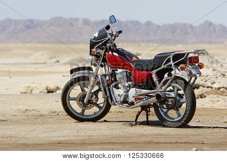 Motorcycle of red and black colors stands in the desert
