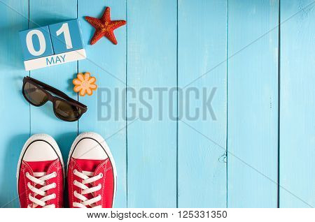 May 1st. Image of may 1 wooden color calendar on blue background.  Spring day, empty space for text.  International Workers' Day.