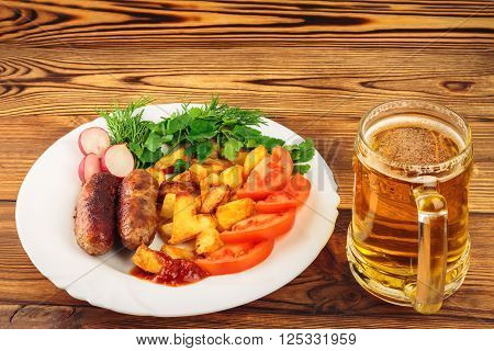 Mug of beer and grilled meat sausages with fried potatoes sliced tomatoes fresh produce and ketchup in plate on wooden table
