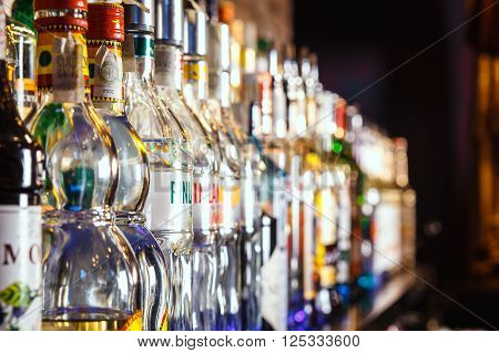 GRODNO BELARUS - NOV 7 2015: Blurred alcohol bottles on a bar at the gastrobar HOUDINI in Grodno Belarus November 7 2015