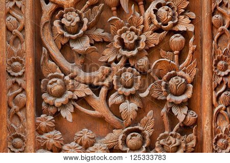 Flowers carved on a wooden board of ancient door of Buddhist temple in Chiang Mai Thailand.