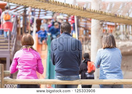 Unrecognizable parents looking at their children who having fun at playground