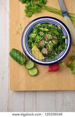 Tabouleh - a bowl of fresh mediterranean green salad arranged with green vegetables.