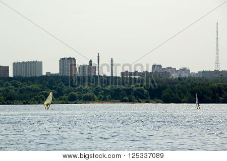 two windsurfers surf in lake in the city
