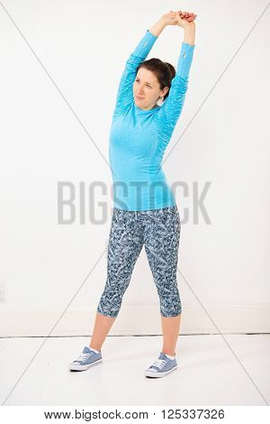 Young woman in blue fitness shirt stretch, shoot over grey background