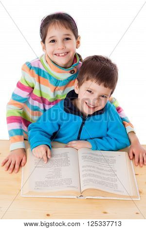 Two happy little kids reading the book at the table, isolated on white