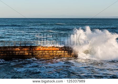 La Jolla Children's pool at high tide with crashing wave.