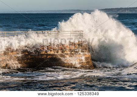 Massive wave crashing into seawall of the La Jolla Children's pool.