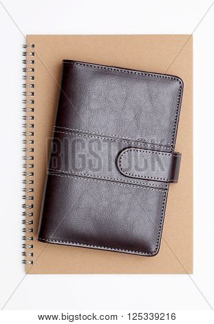 brown leather organizer and spiral notebook on white background